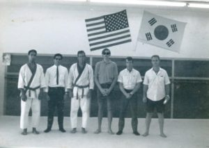 Victor Martinov in shirt and tie with Chuck Norris at his school